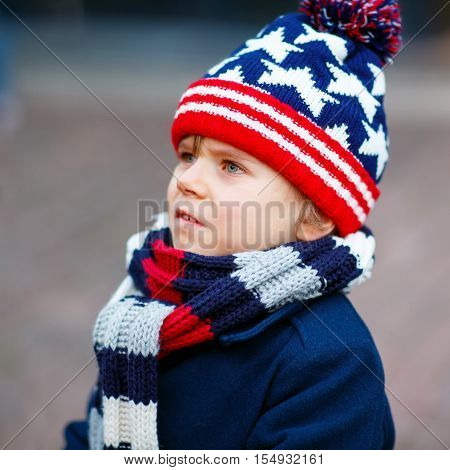 Little cute kid boy crying on Christmas market in Germany, outdoors. Sad child.