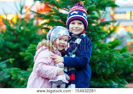 Two little smiling kids, boy and girl with christmas tree. Happy children in winter clothes on Christmas market with lights on background. Brother and sister looking at the camera. Family, tradition, holiday concept