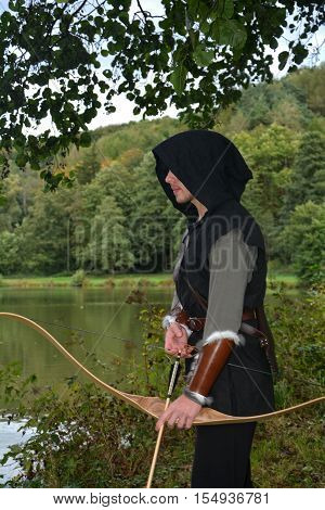 Medieval archer with black hood with the curve span before a lake and looks aside