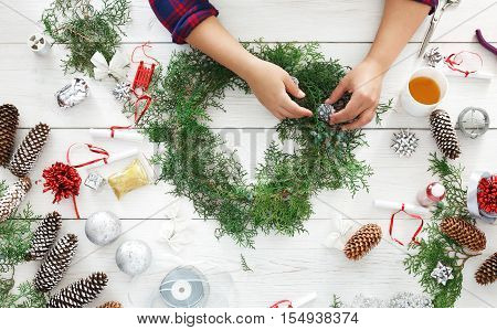 Creative diy craft hobby. Making handmade craft christmas ornaments and fir tree garland. Woman's leisure, tools and trinkets for holiday decorations. Top view of white wooden table with female hands.