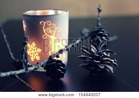 home d cor on the table candle in a glass lamp and dry larch branch
