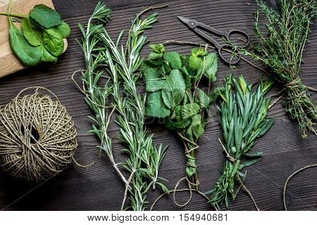 bundle of sage and thyme, mint, estragon, rosemary on wooden background top view.