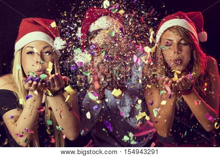 Three young people wearing Santa's hats blowing colorful conffeti at midnight at New Year's Eve party