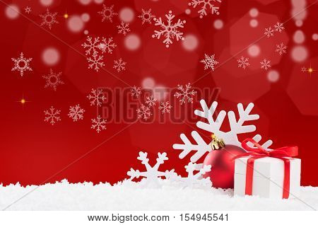 Christmas background with snow and gift box with red ribbon. White snowflakes and red xmas ball with copy space. Christmas decoration with red shiny background.