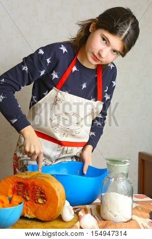 teenager girl cooking pumpkin cake for halloween close up photo