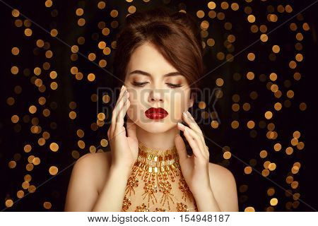 Makeup. Beautiful Young Woman With Bronzed Skin Touch Her Face. Luxury Gold. Gorgeous Girl. Vogue St