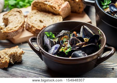 Mussels prepared at home with bread on old wooden table