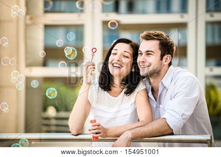 Young couple have great time together with bubble blower - outside in street