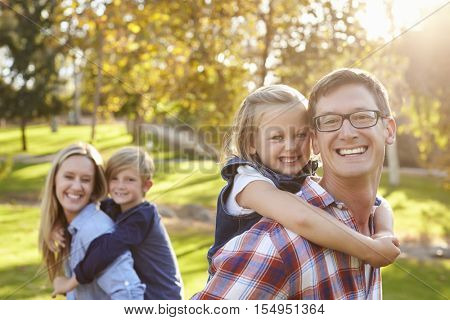 Parents carry their kids piggyback in a park selective focus