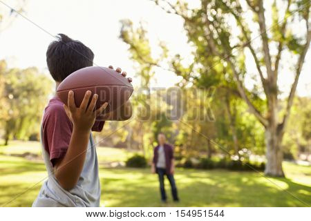 Young boy throwing ball to dad in park, focus on foreground