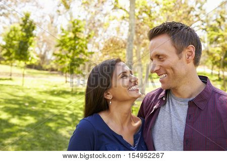 Happy mixed race couple in park looking at each other