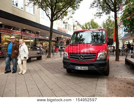 KEHL GERMANY - OCT 18 2016: red Mercedes-Benz delivery van in front of Woolworth retail store in typical German street with senior couple walking on a promenade