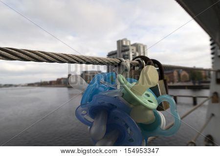 COPENHAGEN DENMARK - OCTOBER 25 2016: The pacifiers on a bridge over Copenhagen harbor. Soothers together with locks of love.