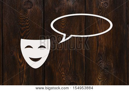 Paper happy mask is talking. Conversation. Emotion concept. Dark wooden background. Abstract conceptual image with copyspace