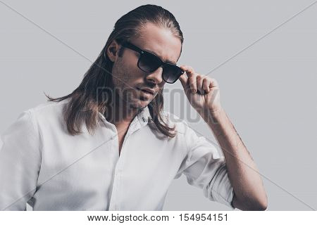 Charming heartbreaker. Handsome young man in white shirt standing against grey background
