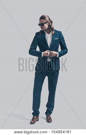 Handsome heartbreaker. Full length of handsome young man in full suit standing against grey background