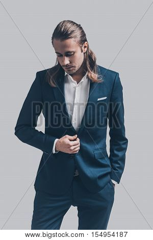 Confident and stylish. Handsome young man in full suit standing against grey background