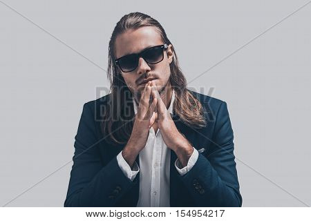 Young and full of confidence. Handsome young man in full suit keeping hands clasped and looking at camera while sitting against grey background