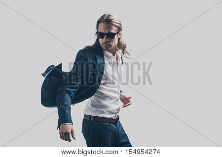 Feeling free and comfortable in his style. Handsome young man in full suit moving in front of grey background