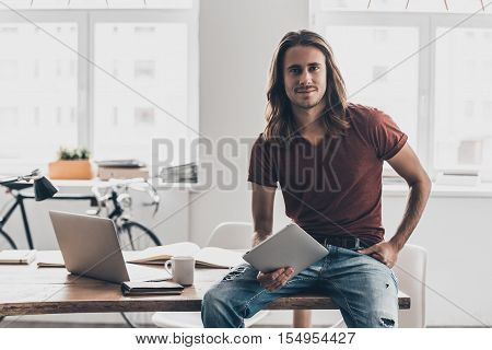 Modern businessman. Handsome young man with long hair holding digital tablet and looking at camera with smile while leaning at the desk in creative office
