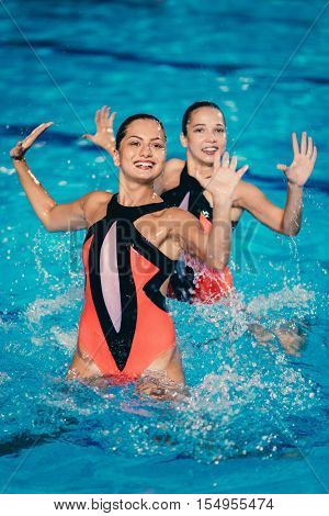 Synchronized swimming duet on performing, toned image, vertical