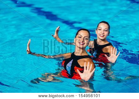 Synchronized swimming duet on performance, toned image