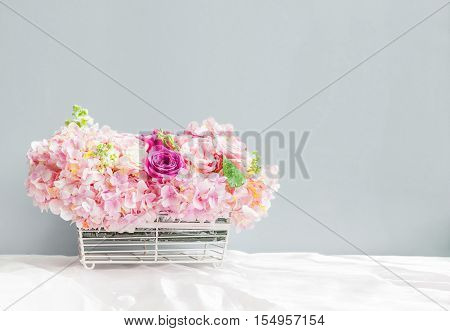 floral basket on the tablecloth in front of the gray wall with copy space flower in basket