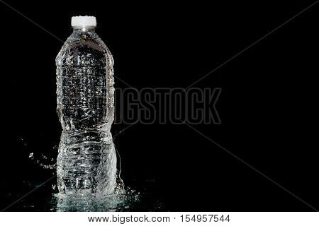 plastic water bottle on wet black background