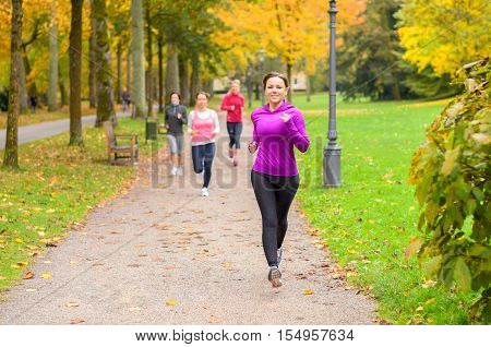 Four Young Woman Out Running Together In A Park