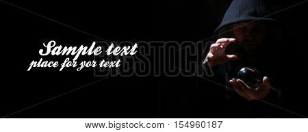 man in a black hood with cristal ball summon evil and empty space for text