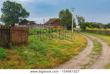 Autumnal scenery with earth road between streets in Boromlya village Sumskaya oblast Ukraine