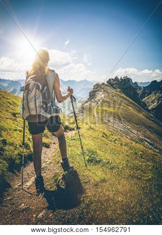 Peaceful view of lone female hiker walking up path towards summit of nearby mountain