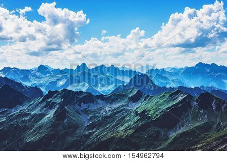 Sharp Alps mountain peaks under vast blue sky with white clouds in Allgau Germany