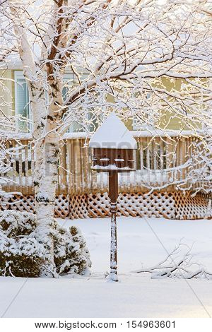 Purple martin birdhouse covered in snow.