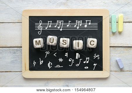 Blackboard in a classroom with some notation symbols. Some wooden cube letters composing the word MUSIC.