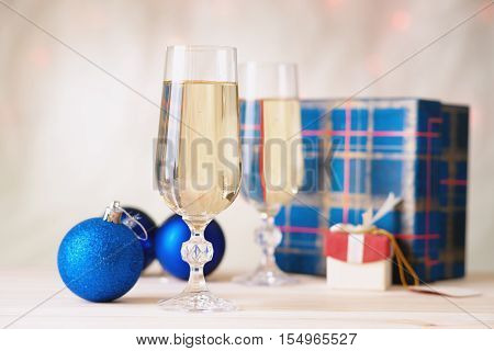 Glasses of champagne with gift boxes and christmas balls