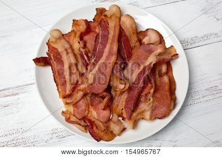 A small white plate of fried bacon strips on a white painted background.