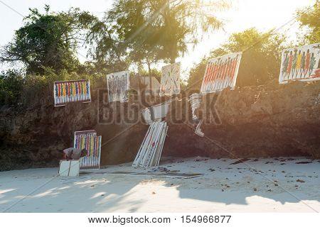 ZANZIBAR, TANZANIYA- JULY 17: tafrican artist with colorful paintings on white canvas on beach on July 17, 2016 in Zanzibar