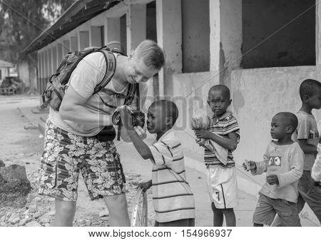 ZANZIBAR, TANZANIYA- JULY 15: cheerful european tourist showing camera to african children on July 15, 2016 in Zanzibar