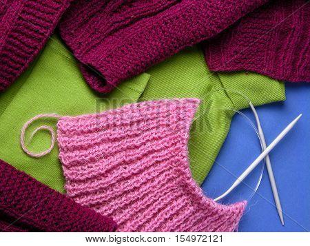 Handmade knitwear, crimson, pink, green. Knitting needles. Texture on a blue background.