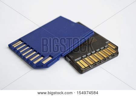 Two isolated plastic blue and black compact memory card (SD card - Secure Digital card) used in cameras, computers and video cameras in a blue color with metal connectors in the golden color poster