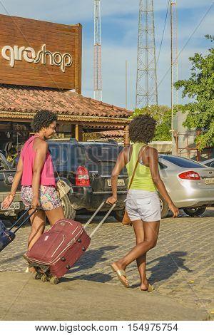 PORTO GALINHAS, BRAZIL, JANUARY - 2016 - Two young women with baggage arriving at Porto Galinhas Pernambuco Brazil