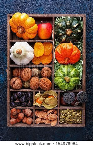 Set of autumn vegetables fruits nuts and seeds in a wooden box with cells top view