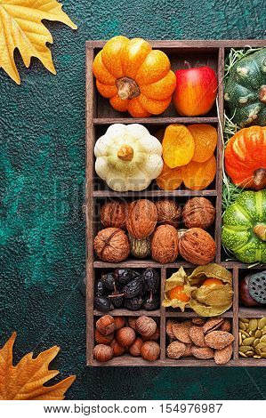 Set of autumn vegetables fruits nuts and seeds in a wooden box with cells top view with copy space