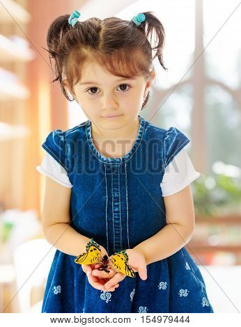 Adorable little girl with short pigtails on her head, holding a large butterfly, close-up.In a room with a large semi-circular window.