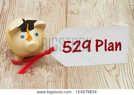 Your 529 education savings plan A golden piggy bank and grad cap on a desk with a gift tag with text 529 Plan