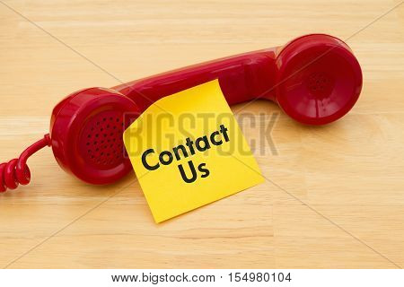 How to contact us A retro red phone with yellow sticky note on a desk with text Contact Us