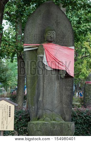 Tokyo Japan - September 26 2016: Statue of Buddha in front of Stela at Senso-ji Buddhist Temple. Serene image. He wears a red apron. Green foliage signs.
