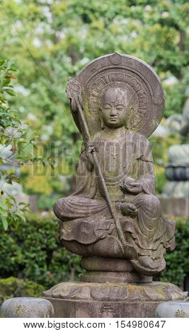 Tokyo Japan - September 26 2016: Closeup of stone statue of Bodhisattva sitting on lotus pedestal in garden at Senso-ji Buddhist Temple. Large halo. Holds staff and sphere. Green foliage.