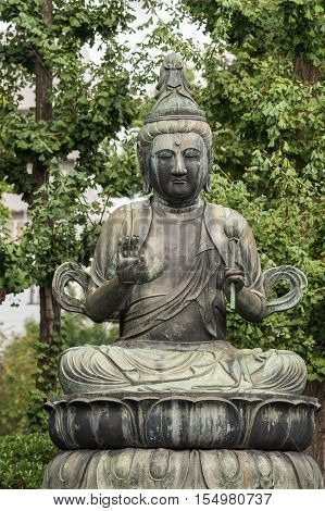 Tokyo Japan - September 26 2016: Closeup of bronze statue of Seishi Bosatsu attendant of Amida Buddha sitting on lotus pedestal in garden at Senso-ji Buddhist Temple. Green foliage.